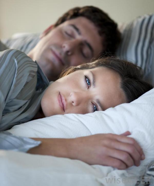 woman-experiencing-insomnia-near-sleeping-man
